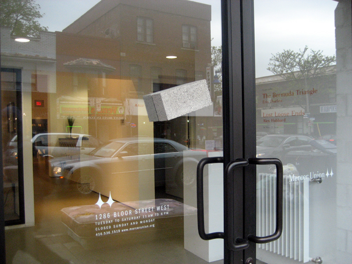 """Narcissus Stops To Look At His Dumb Reflection , dimensions variable (2 bricks = 2.25"""" x 3.5"""" x 8.5"""" each), two bricks attached with silicon to either side of gallery storefront window, 2010"""