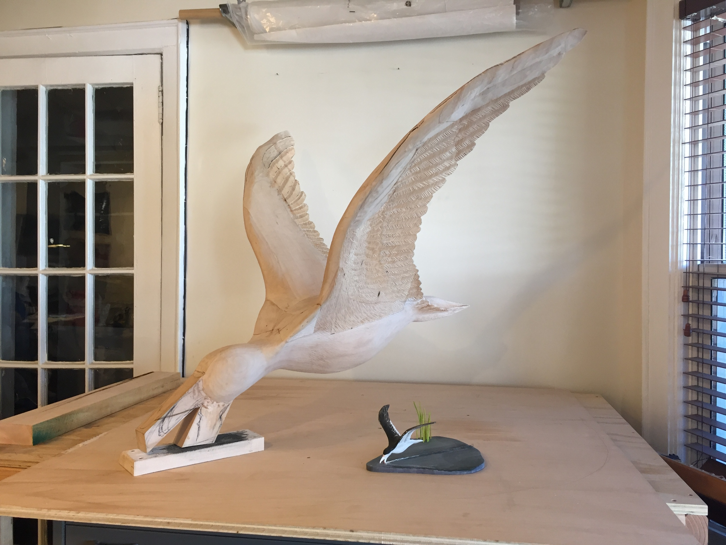 The maquette and full scale work next to each other. Next steps involve buying more wood and carving the base, along with continued carving on the wings, the body and the beak..