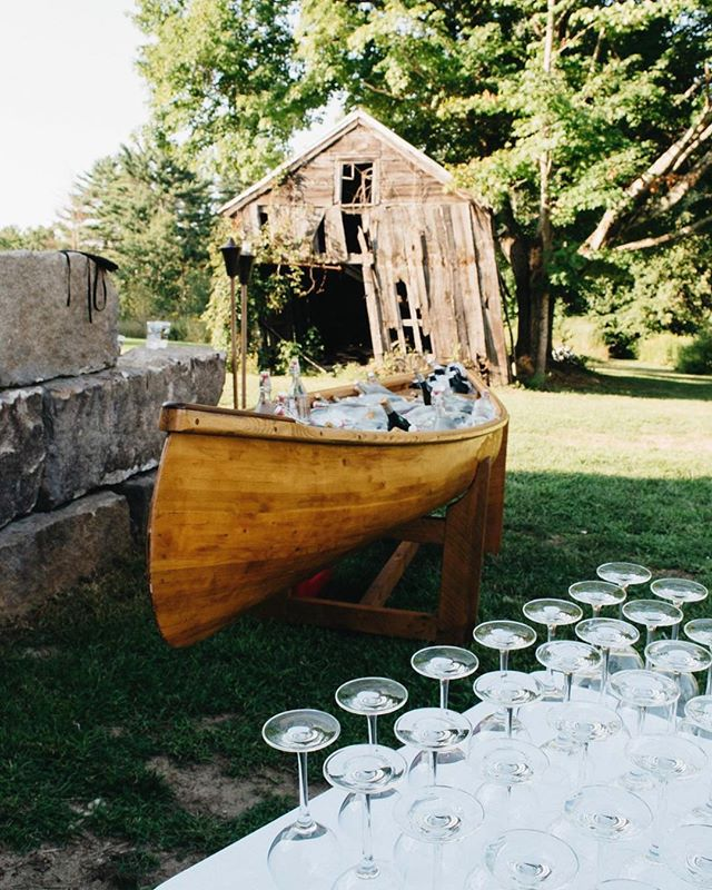Our rustic canoe filled with local beer growlers on ice and crystal glassware for the wine selection 👌
