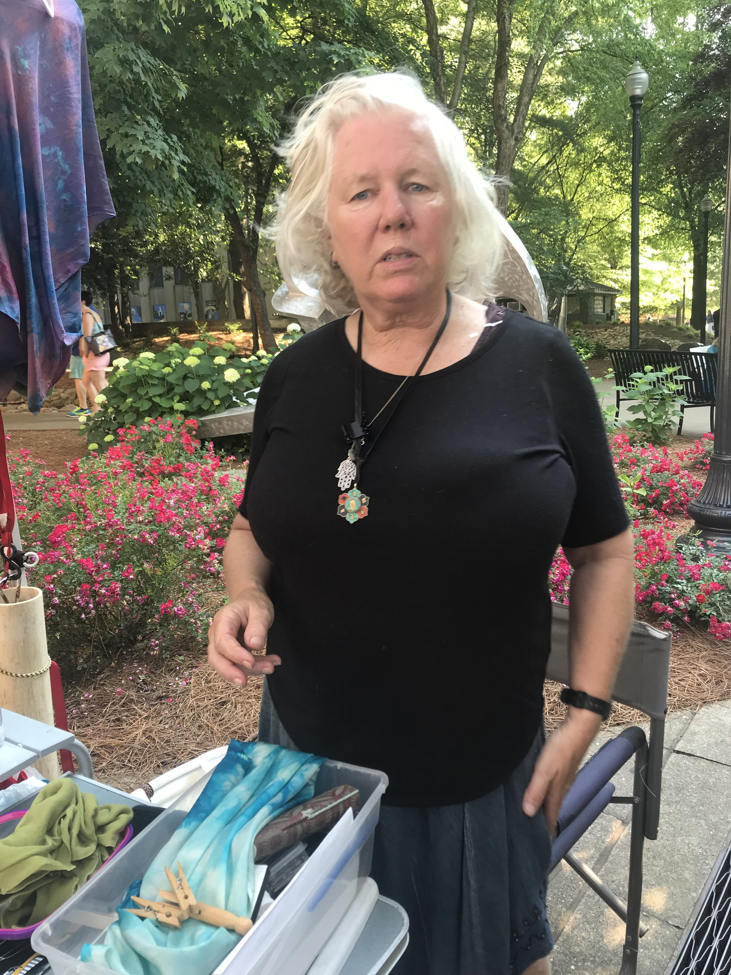 Fiber artist Nancy Roberson pauses at her RichRobes booth. Nancy sells handwoven wearables, shibori silks and tapestries