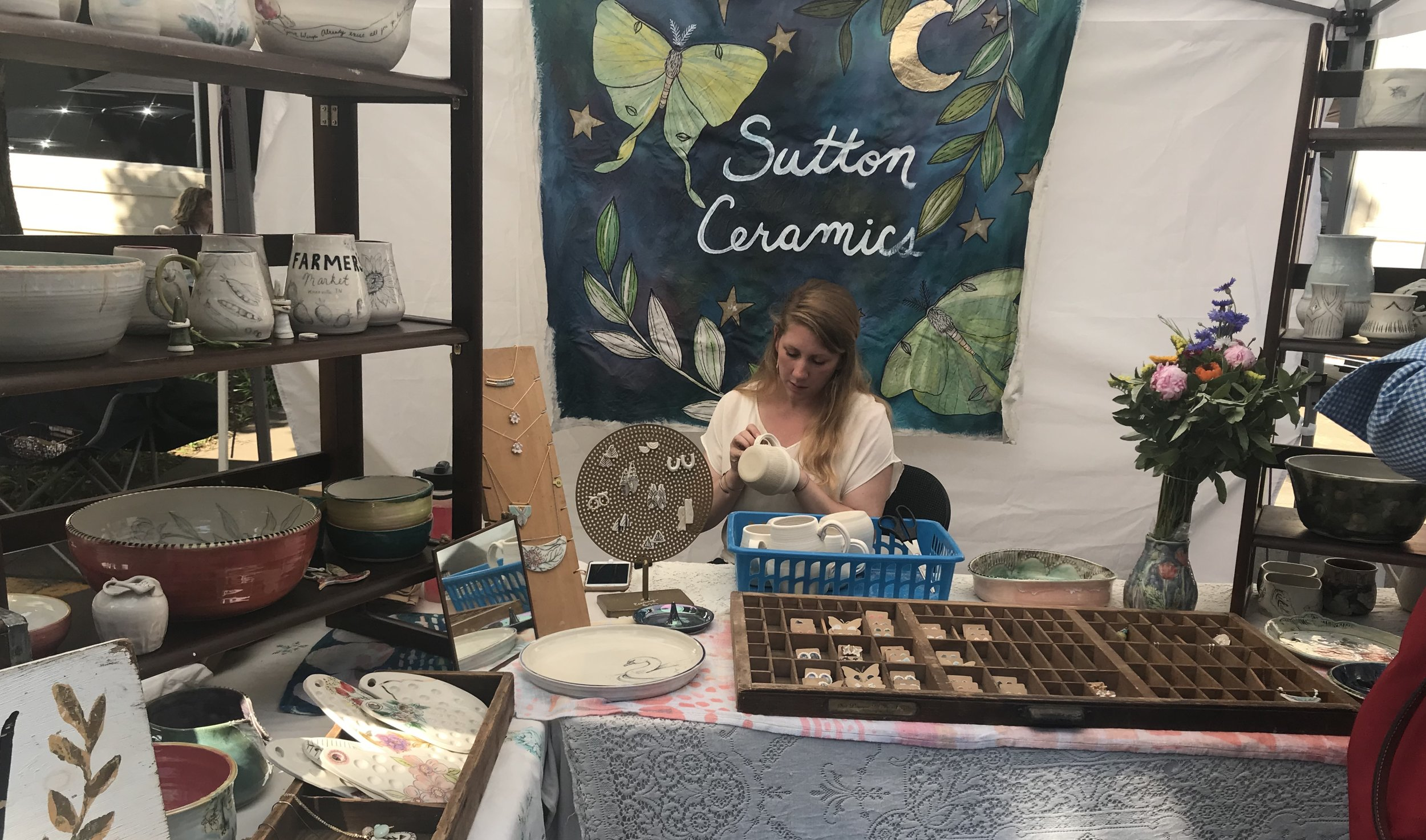 Lacey Sutton works on a piece at her ceramics booth