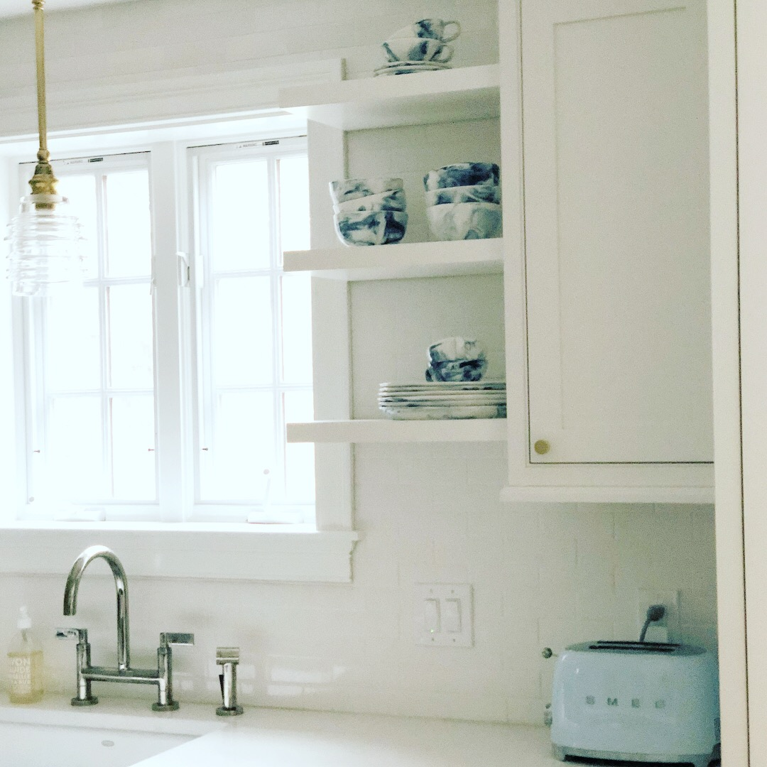 "The white ultramodern handmade porcelain subway tiles with a crackle finish reach all the way to the ceiling. ""On each side of the sink, we put floating shelves for the everyday 'china',"" says Jerde. Pictured is blue-swirled ""Strata"" dinnerware from Anthropologie."