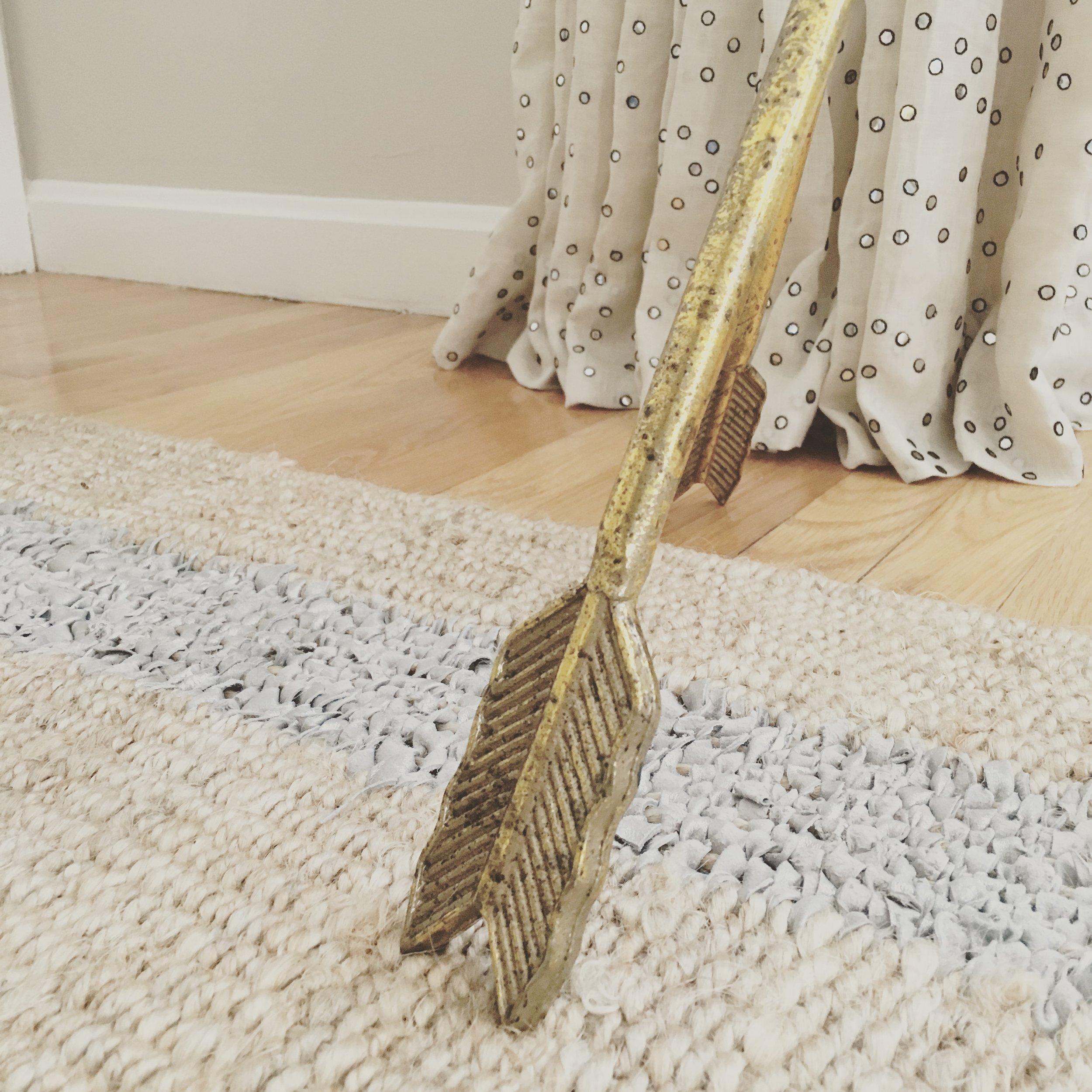 Gold arrow side table leg with a metallic stripe Seagrams rug