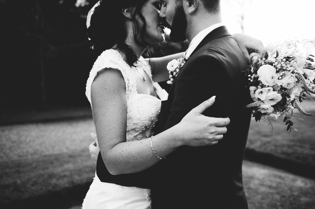 closeup black and white photo of a bride and groom kissing in the gardens at eaves hall wedding.