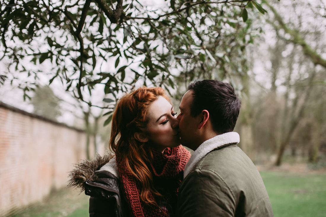 Natural photograph of couple kissing under a tree at Haigh Hall