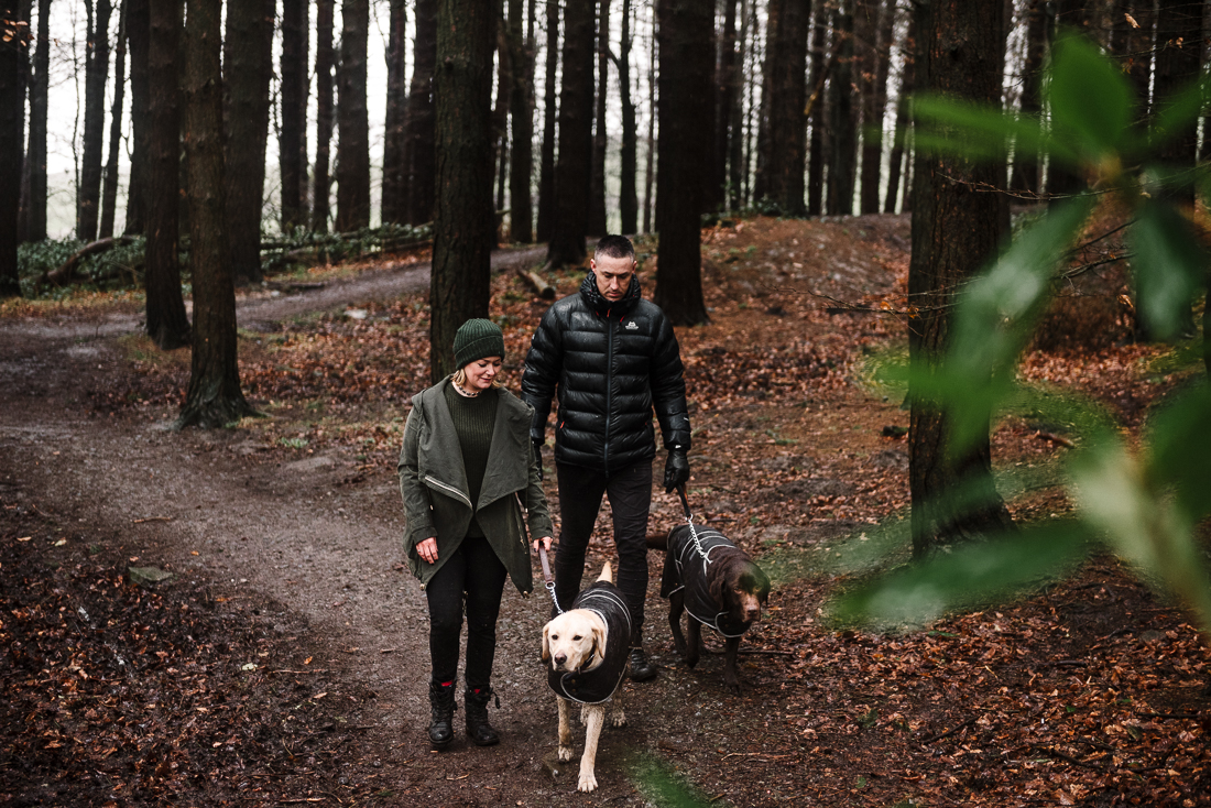 Couple and their dogs walking through the woods at Hurstwood in Burnley, Lancashire.