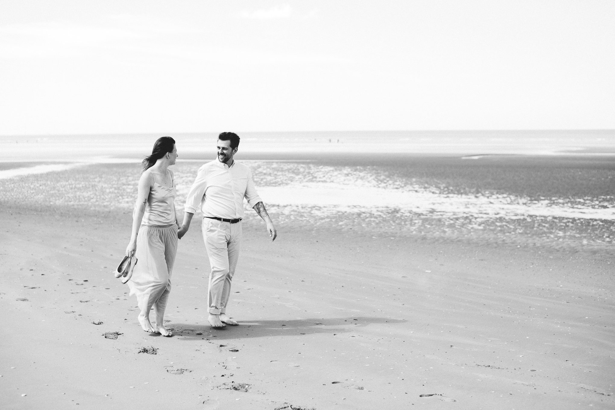Bride and groom holding hands as they walk together along Formby beach.
