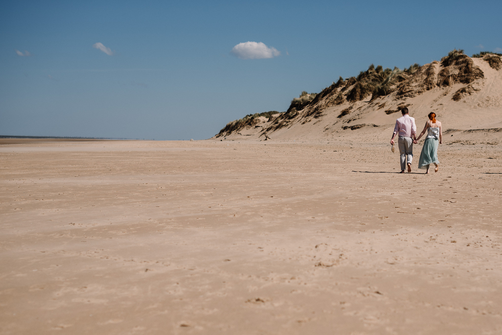 Natural shot of couple walking along the beach towards the sand dunes on Formby beach.