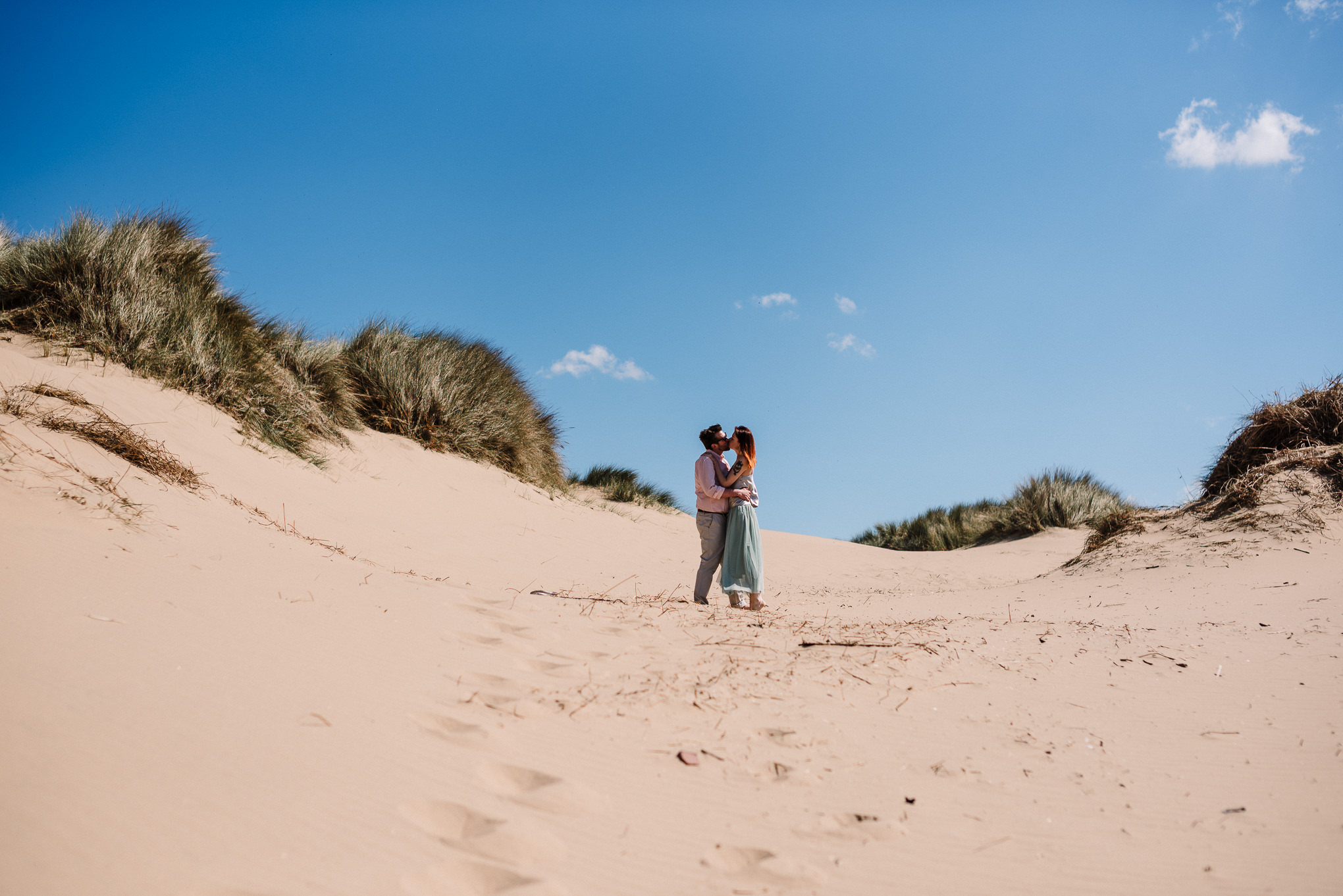 Landscape shot of sand dunes and bride and groom on the beach. Liverpool wedding photography