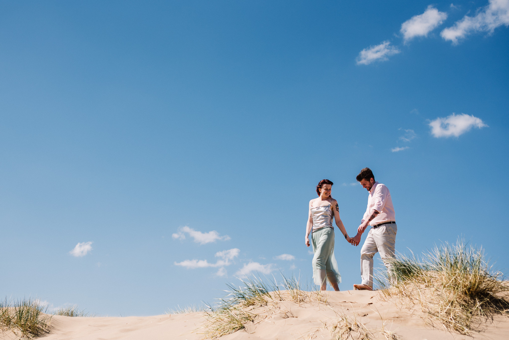 Bride and groom walking on hillside at Formby. Liverpool wedding photography