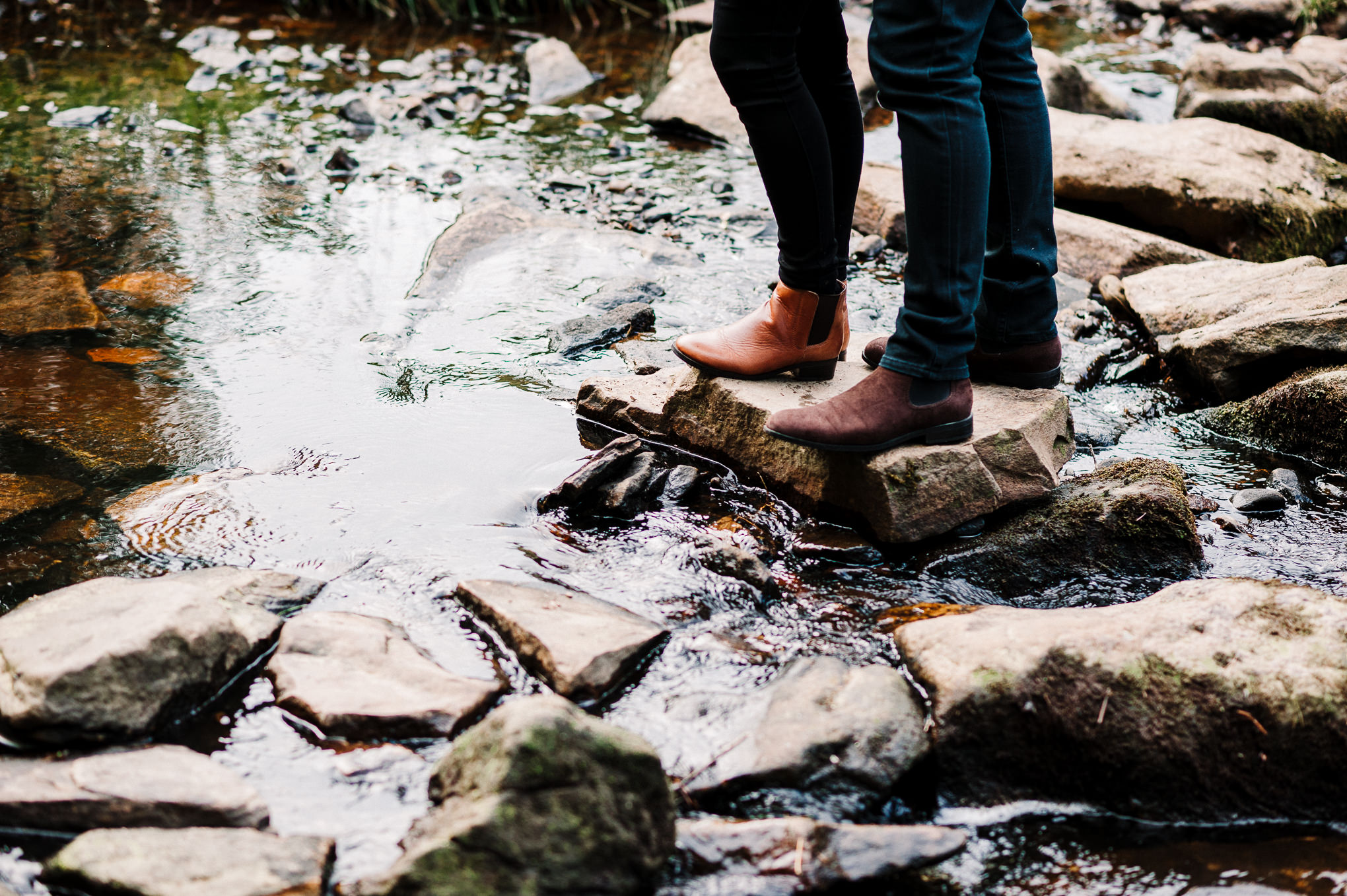 Close up shot of couple stood on stones in the river at Entwistle Reservoir in Bolton, Lancashire.