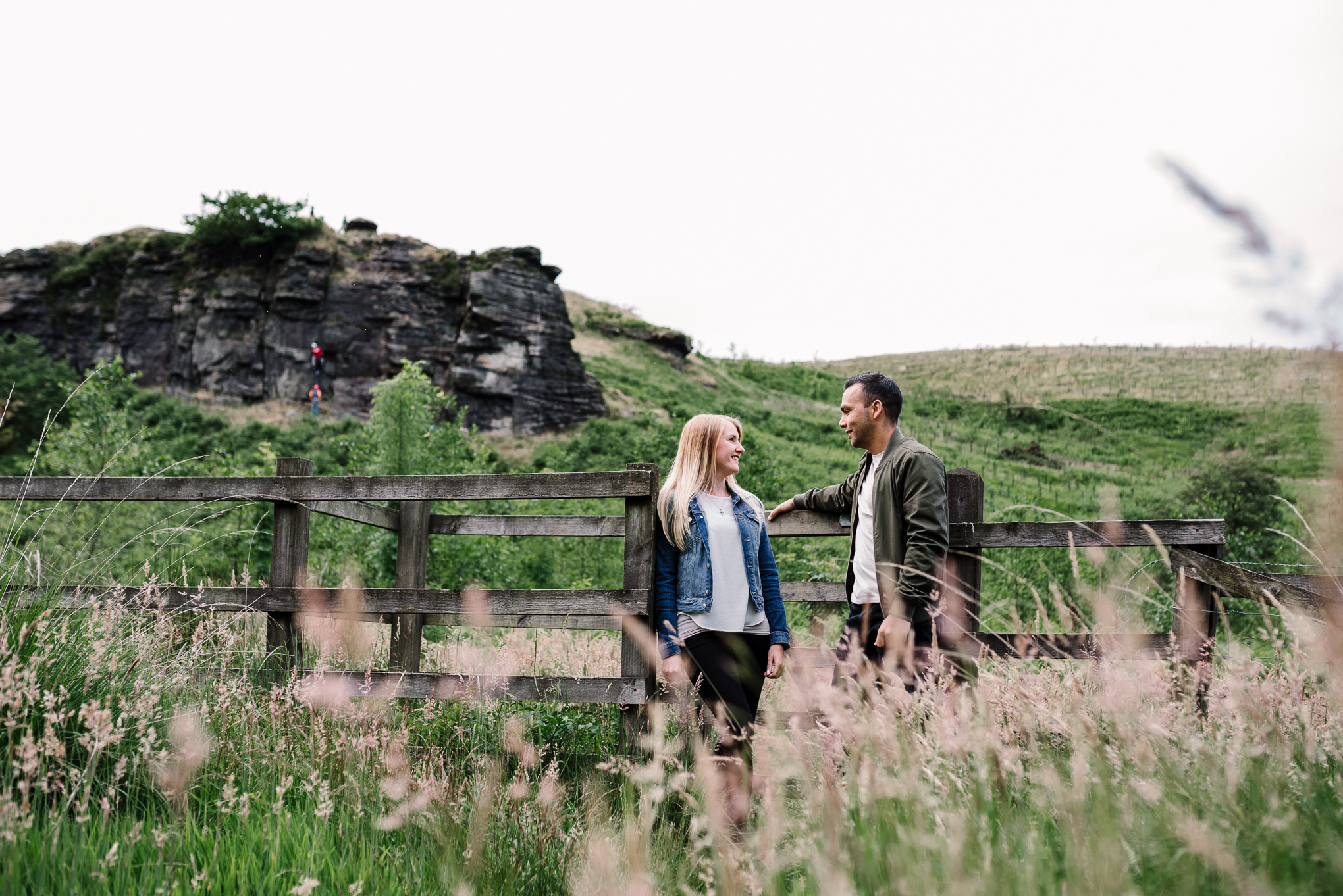 Landscape photo with couple stood naturally at a gate.
