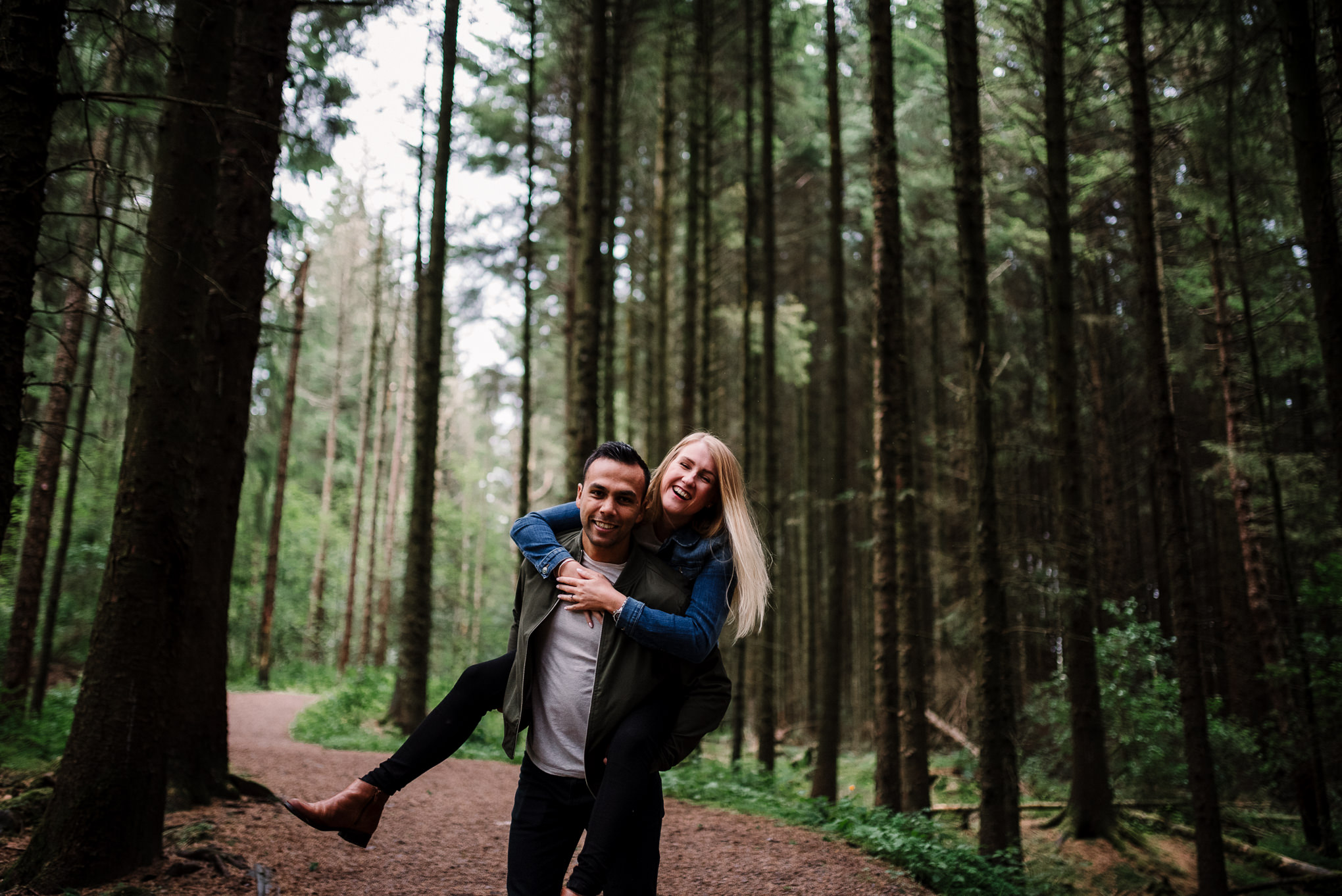 Natural photo of couple running together in the woods at Entwistle Reservoir in Bolton, Lancashire.