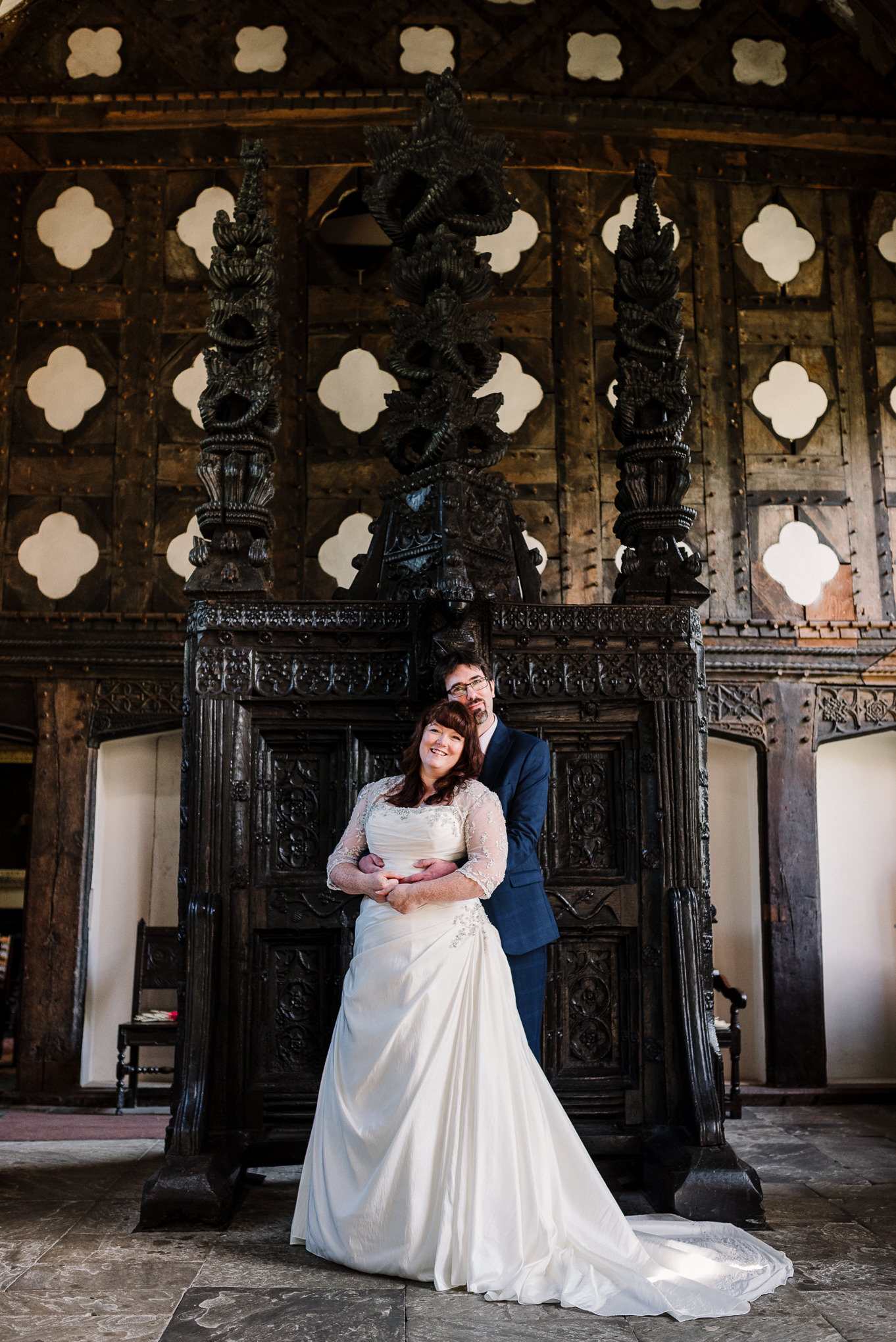 Natural shot of bride and groom in front of the carved oak screen at Rufford Old Hall. Lancashire wedding photography.
