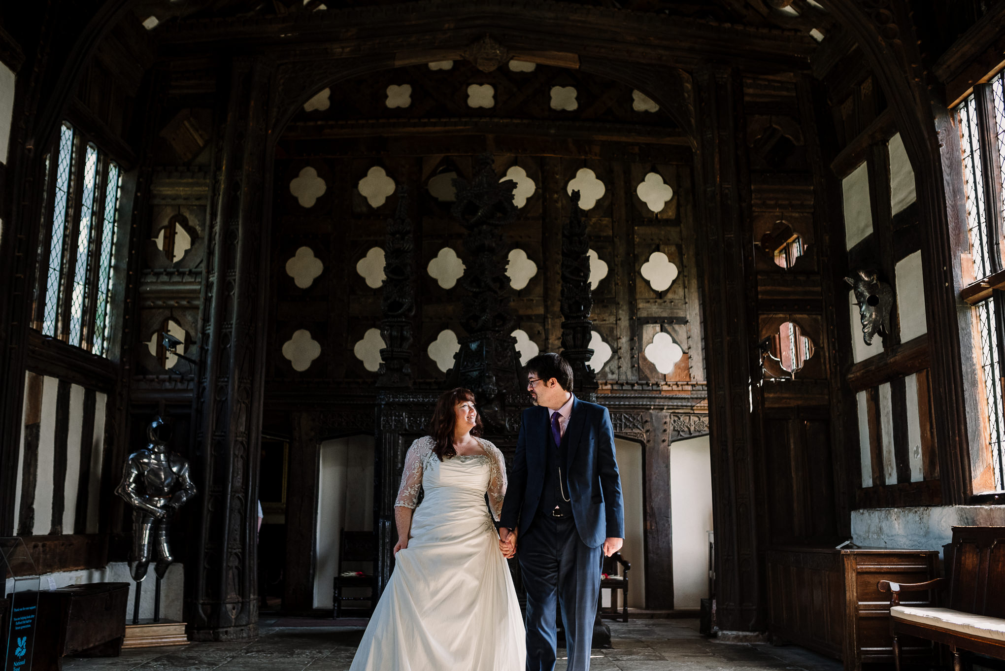 Bride and groom walking through the Great Hall at Rufford Old Hall in Lancashire.