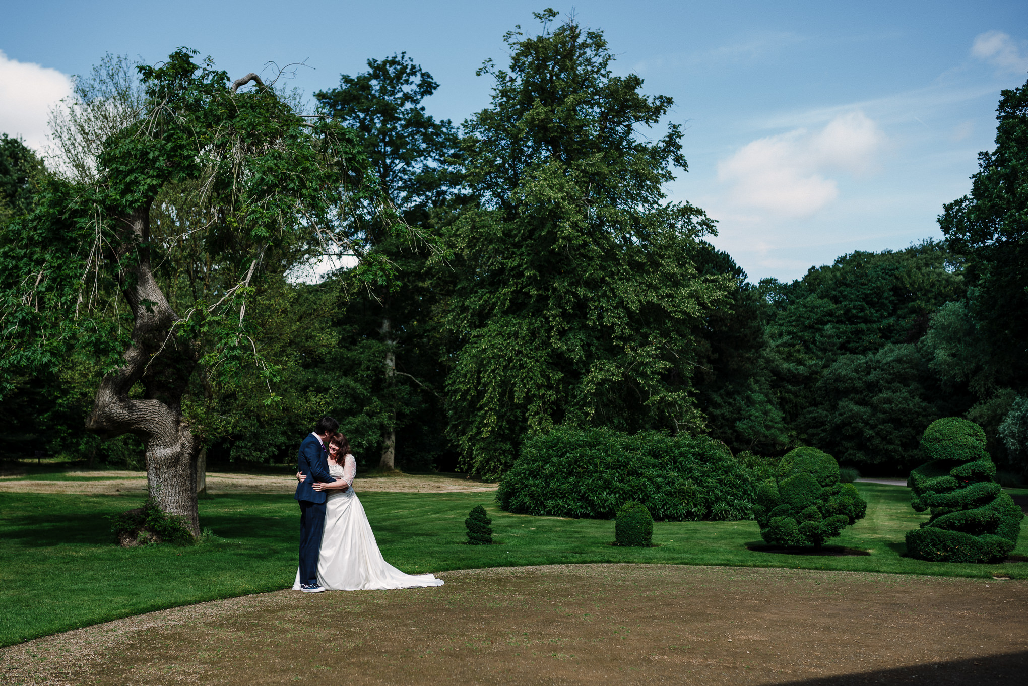 Landscape shot with bride and groom kissing.