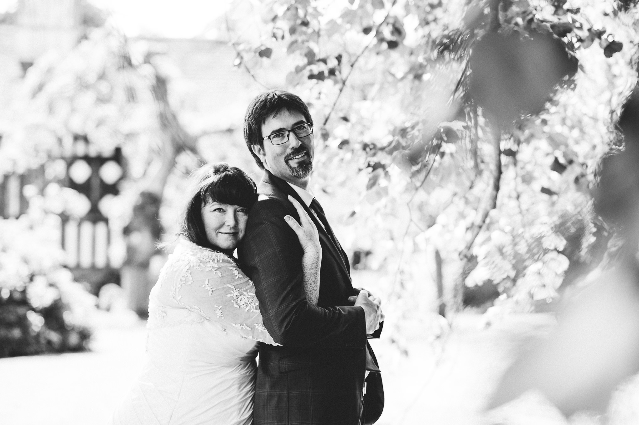 Black and white photograph of bride and groom hugging.