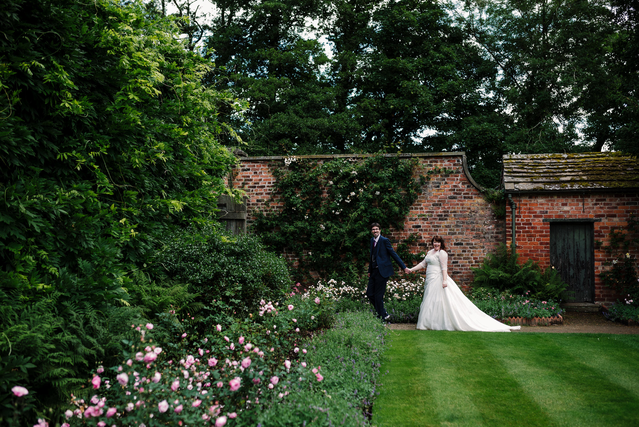 Bride and groom holding hands in the gardens at Rufford Old Hall, Lancashire.