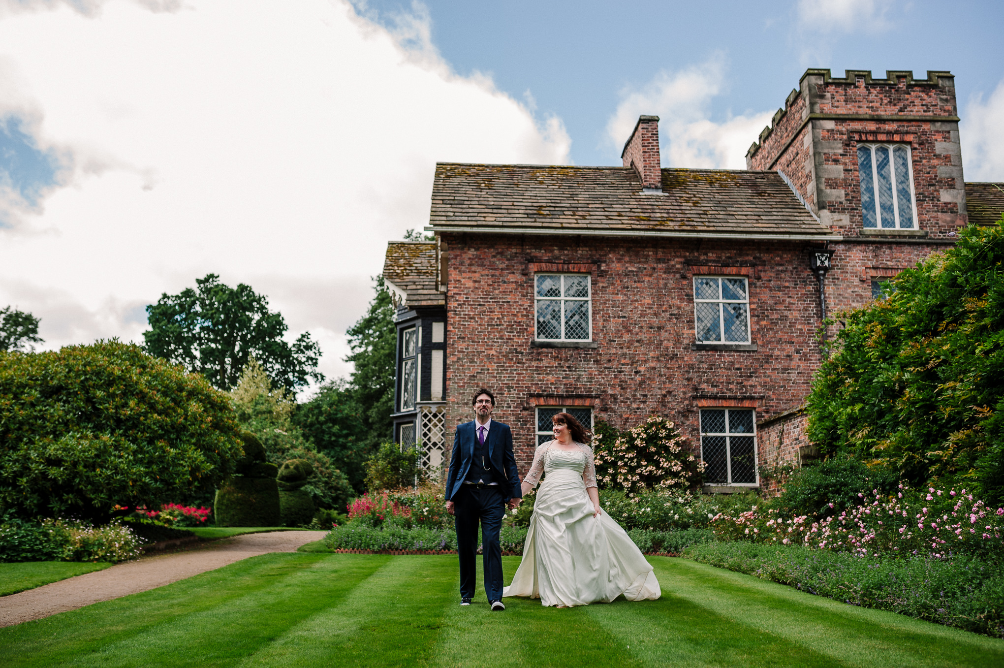 Bride and groom with Rufford Old Hall in the background. Natural wedding photography.