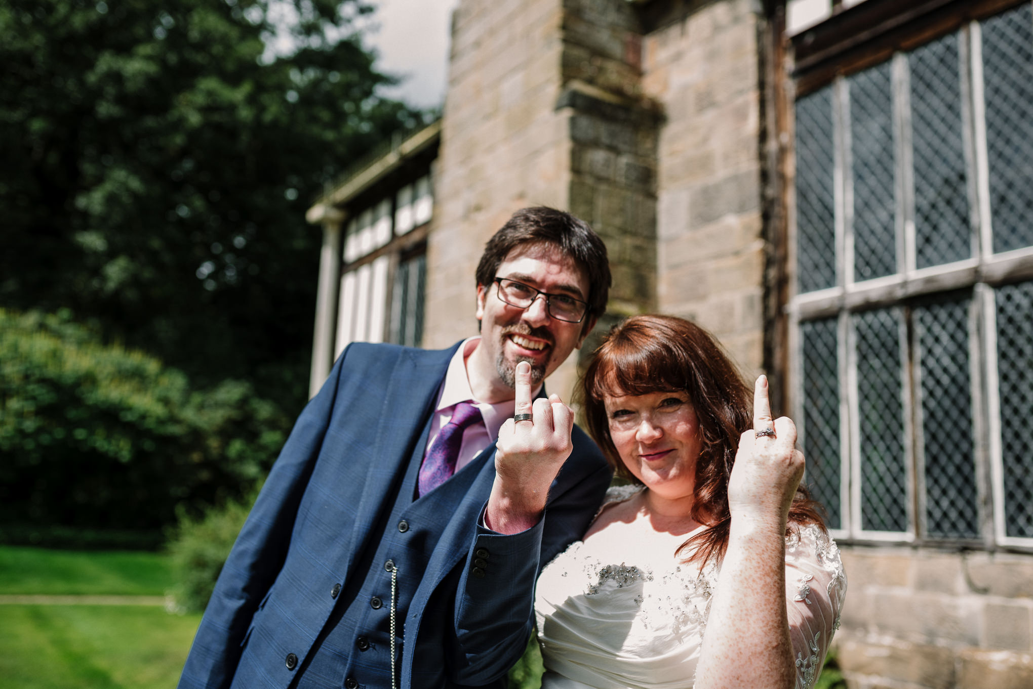 Fun shot of bride and groom showing wedding rings. Lancashire wedding photography.