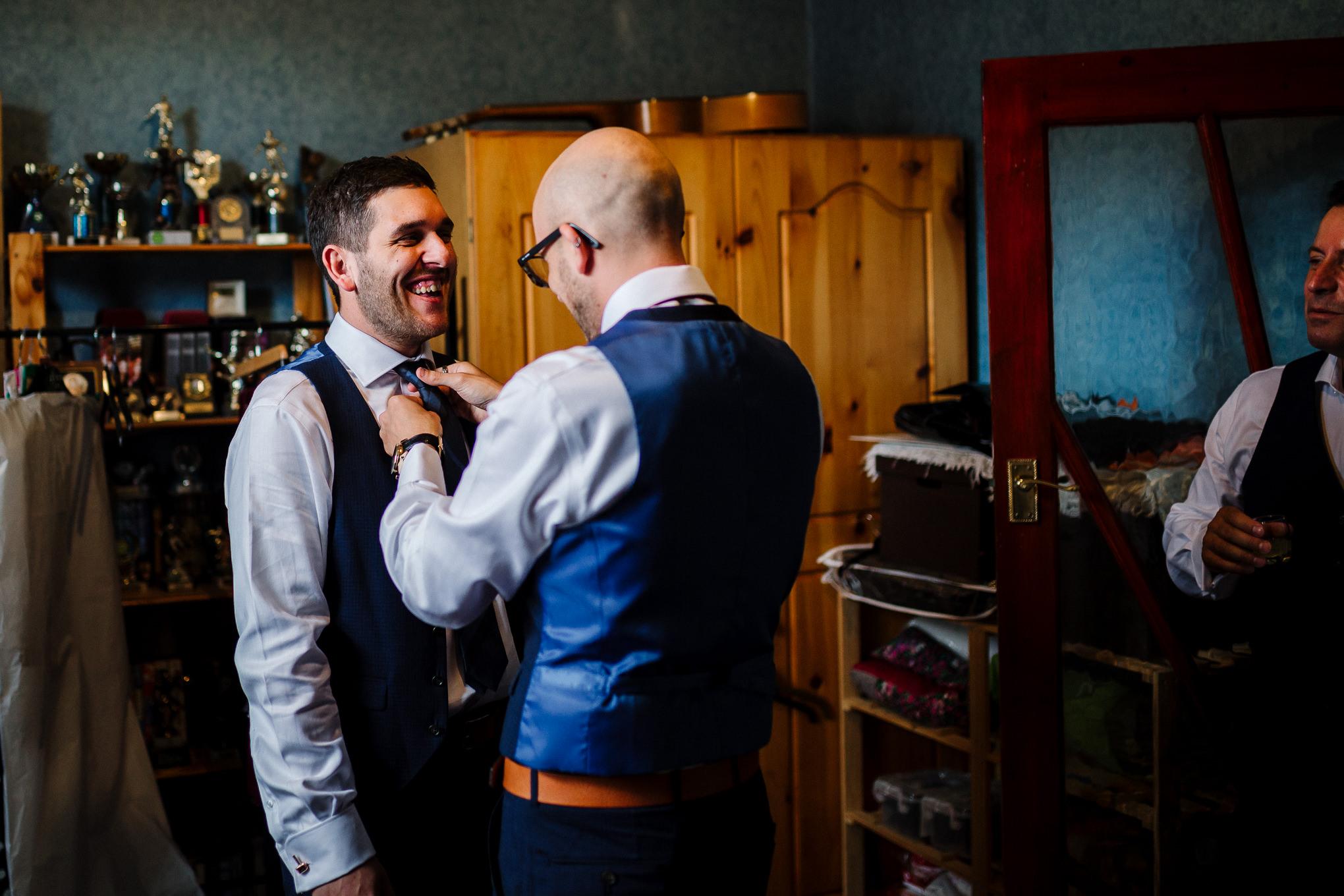 Best man tying the grooms tie.