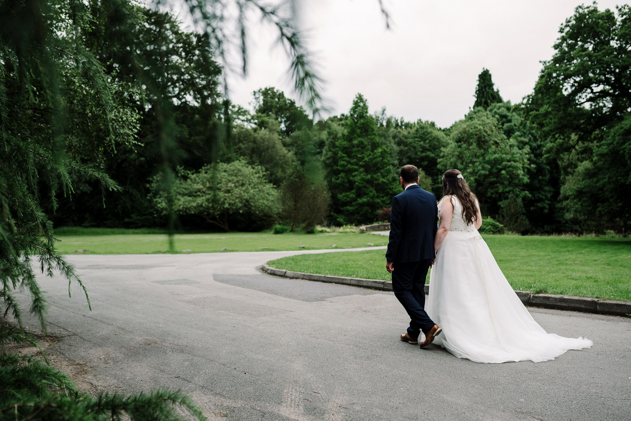 Natural photo of the bride and groom walking through the grounds at Rivington Hall Barn in Lancashire.