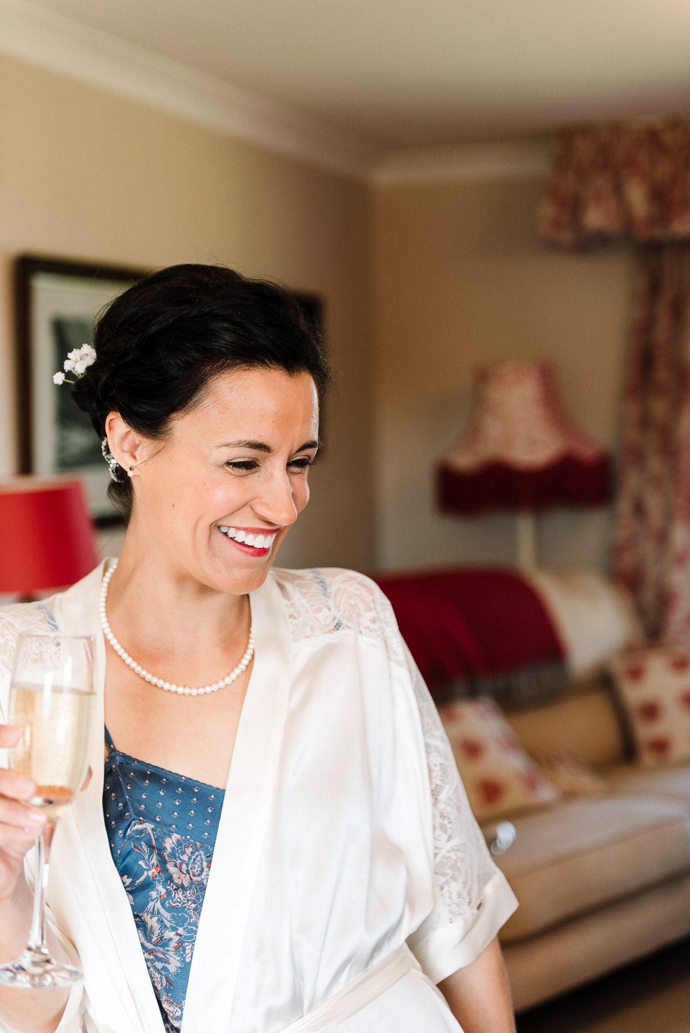 Bride laughing whilst drinking champagne. Relaxed wedding photography