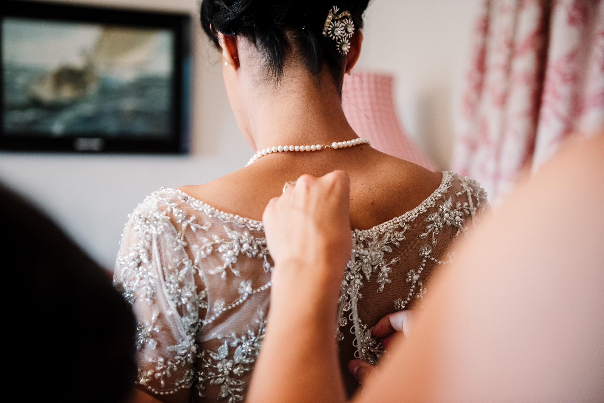 Natural shot of brides dress being buttoned up. Lake District wedding photography