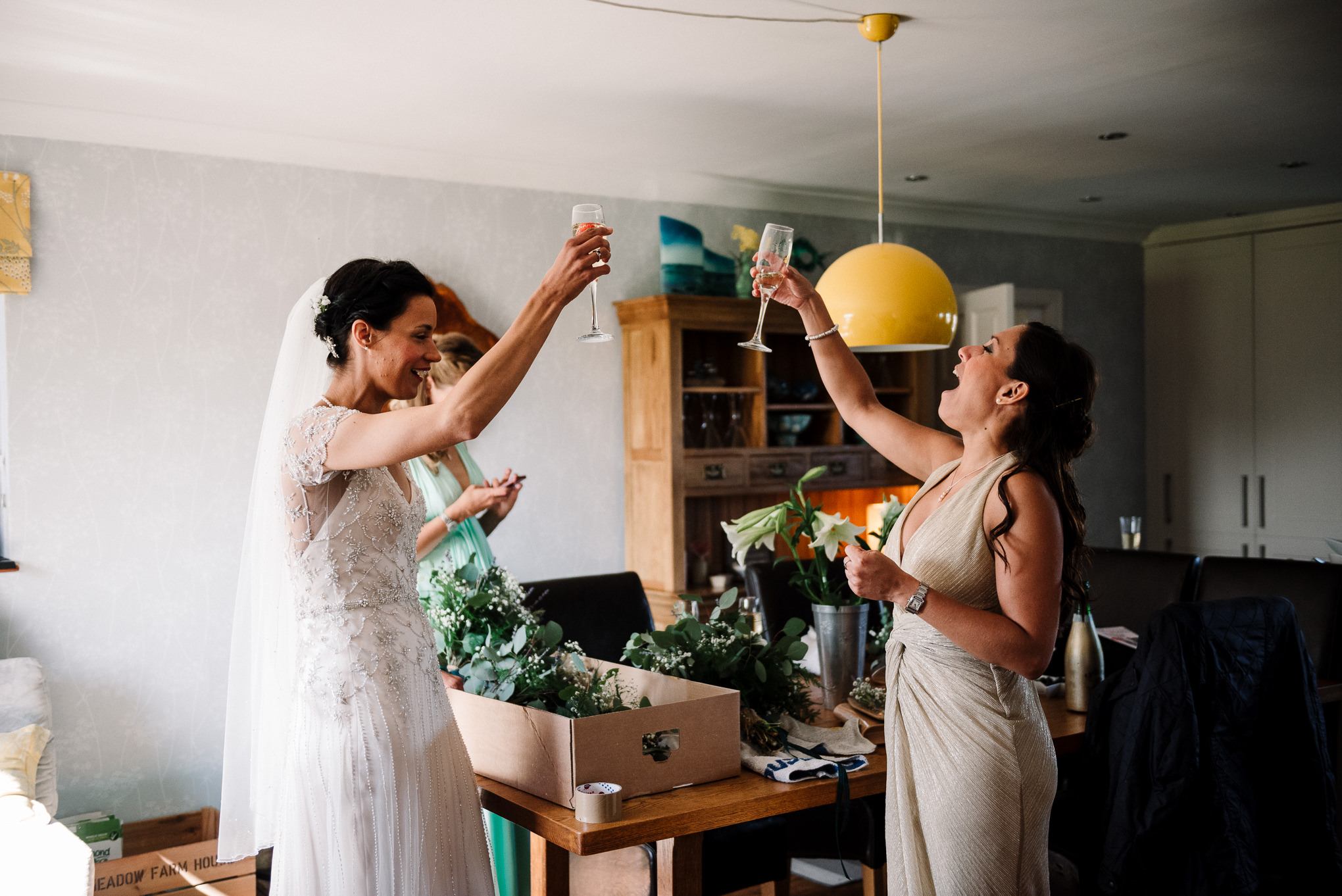 Cheers. Documentary photo of bride and bridesmaid celebrating