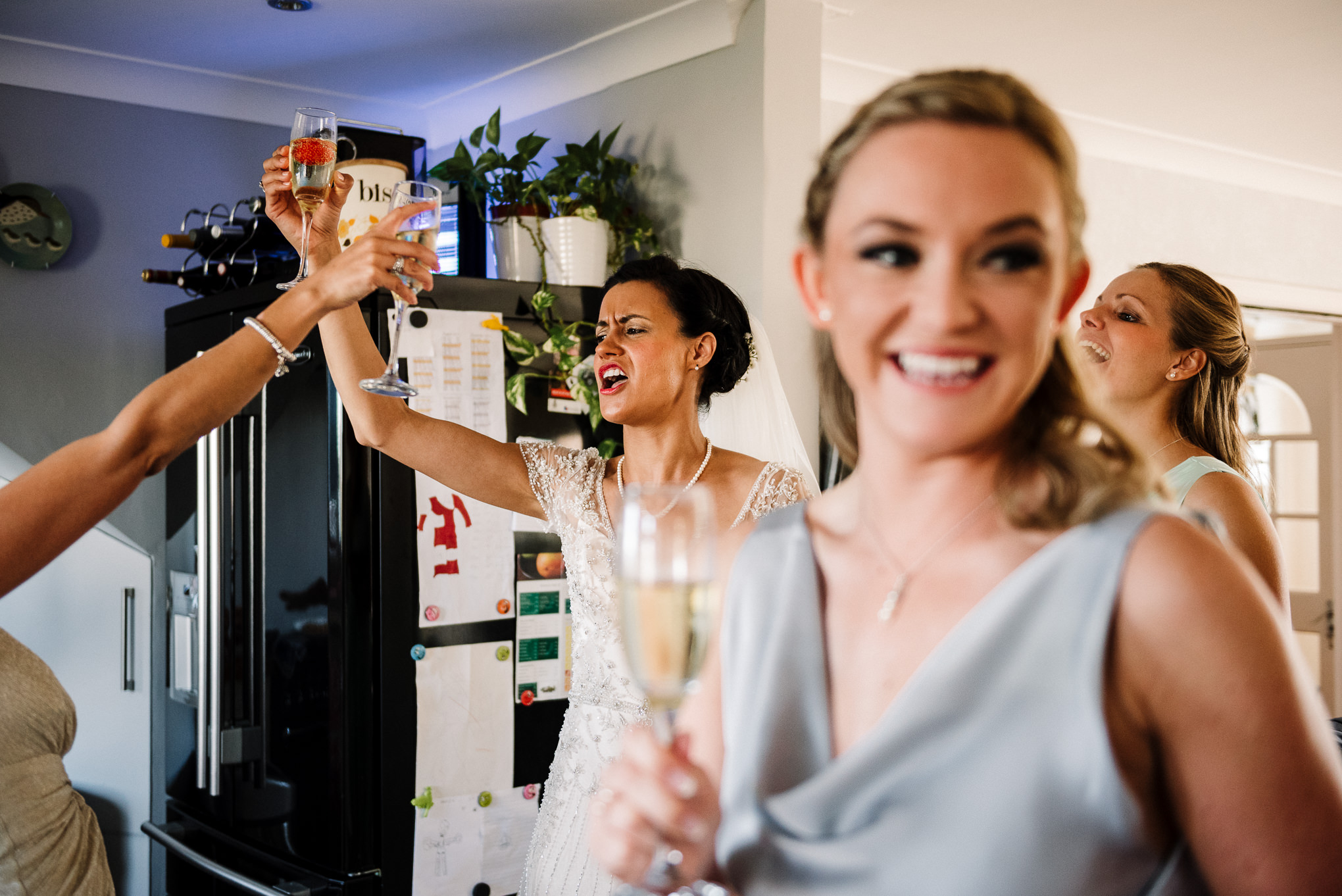 Natural shot of bride singing in the kitchen. Documentary wedding photography