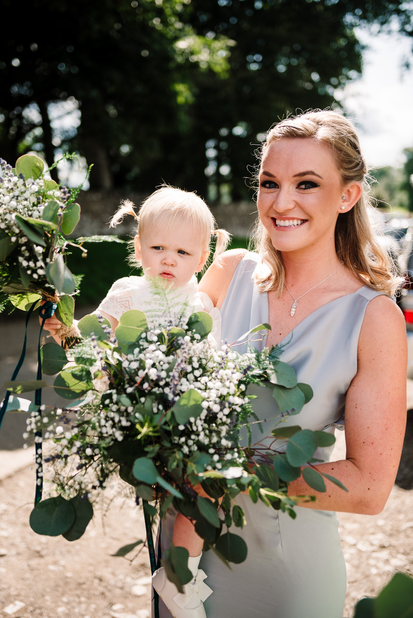 Bridesmaid holding flower girl and rustic bouquet
