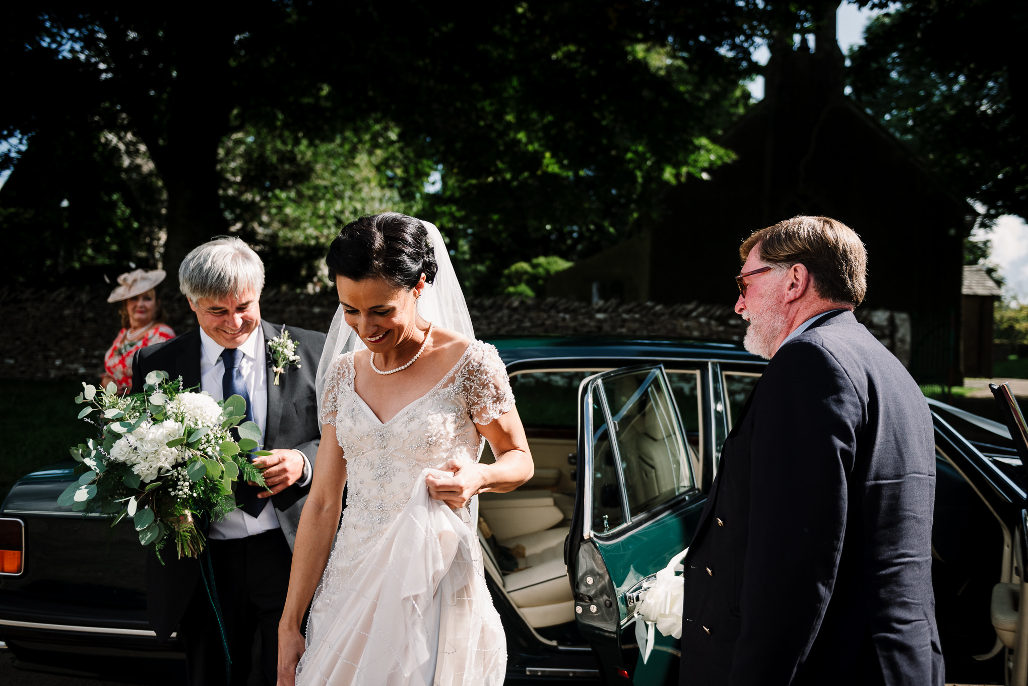 Documentary shot of the bride getting out of the car at church.
