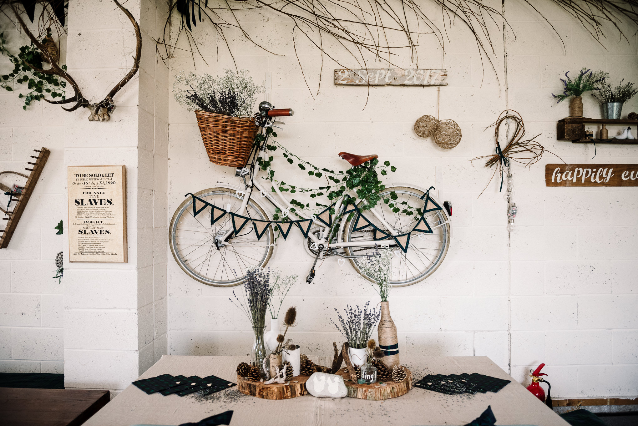 Rustic wedding decor with old vintage bike hung on the wall. Farm wedding photography