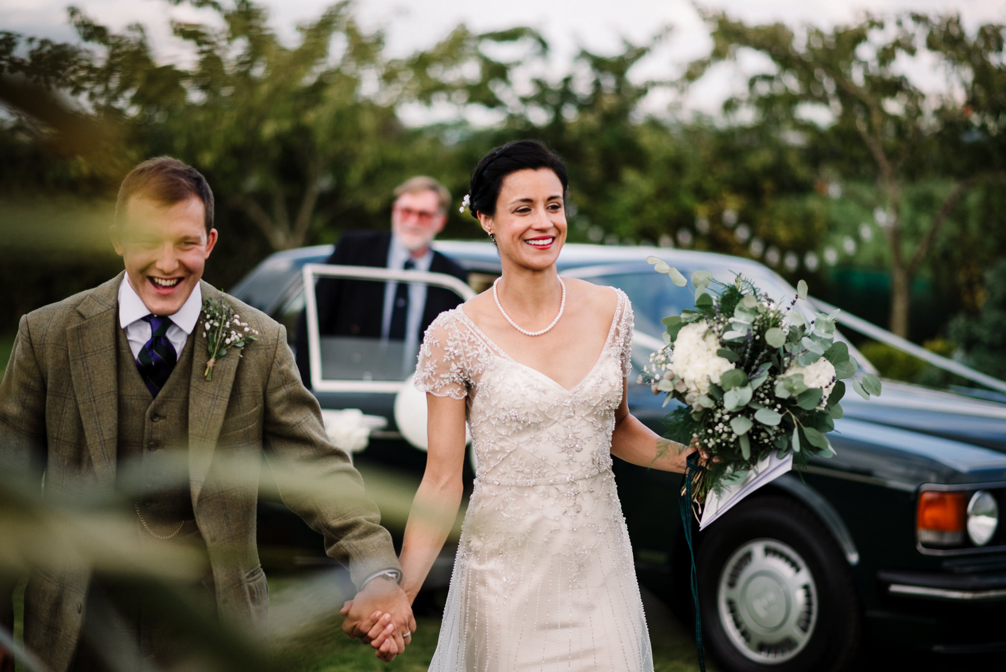 Natural shot of bride and groom walking together after arriving at the farm