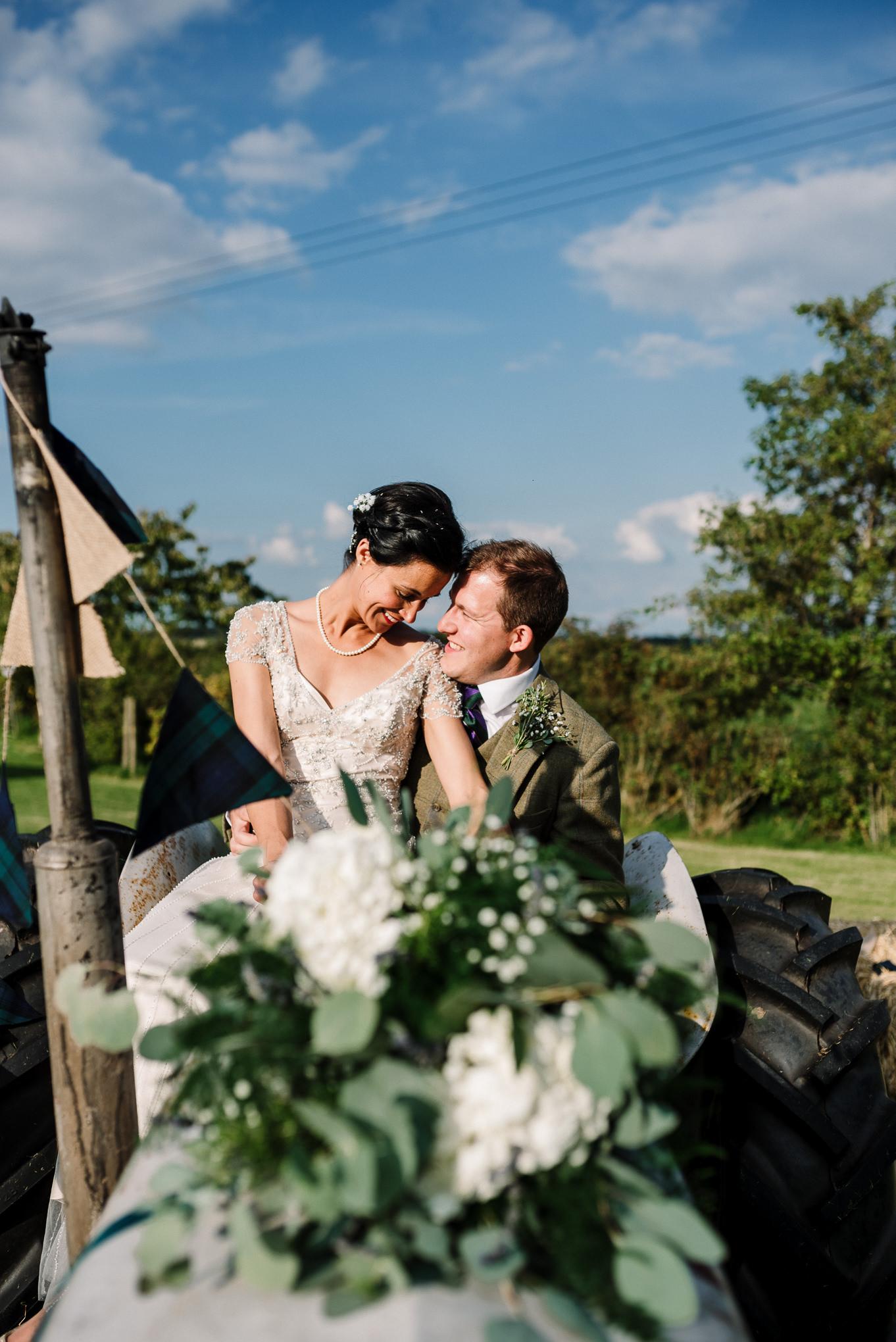 Portrait on the tractor. Farm wedding photography