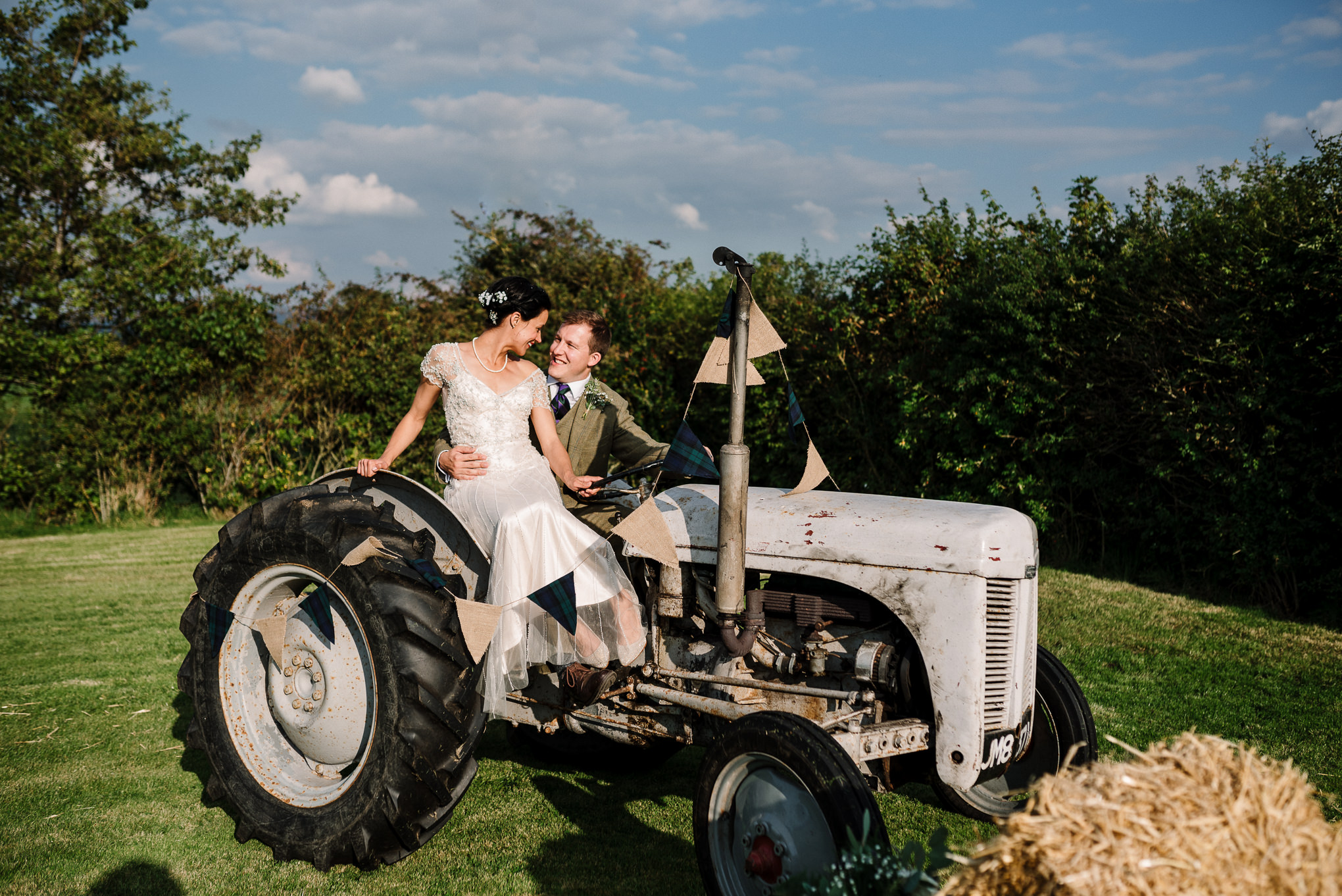 Portrait of bride and groom on the farms tractor. Lake District wedding photographer