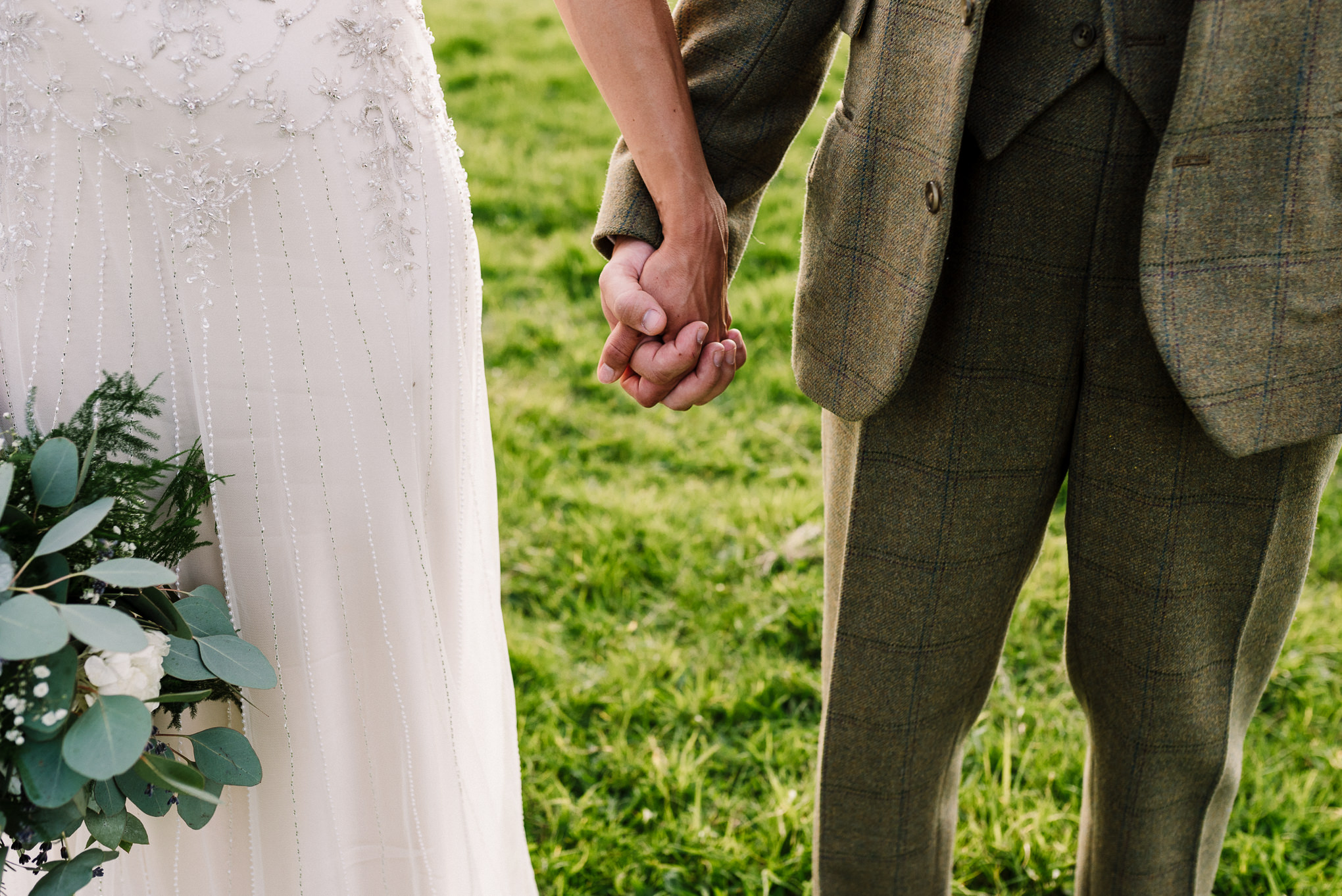 Close up of bride and groom holding hands. Creative wedding photography