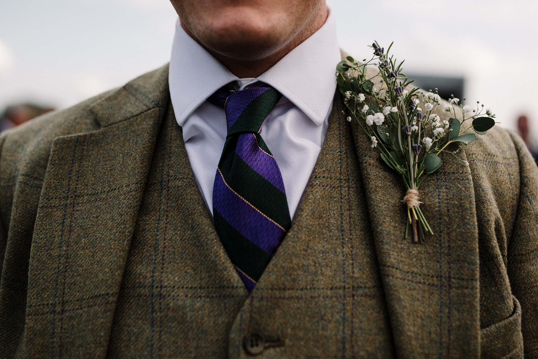 Detailed shot of grooms tweed suit and button hole. Farm wedding photography in the Lake District