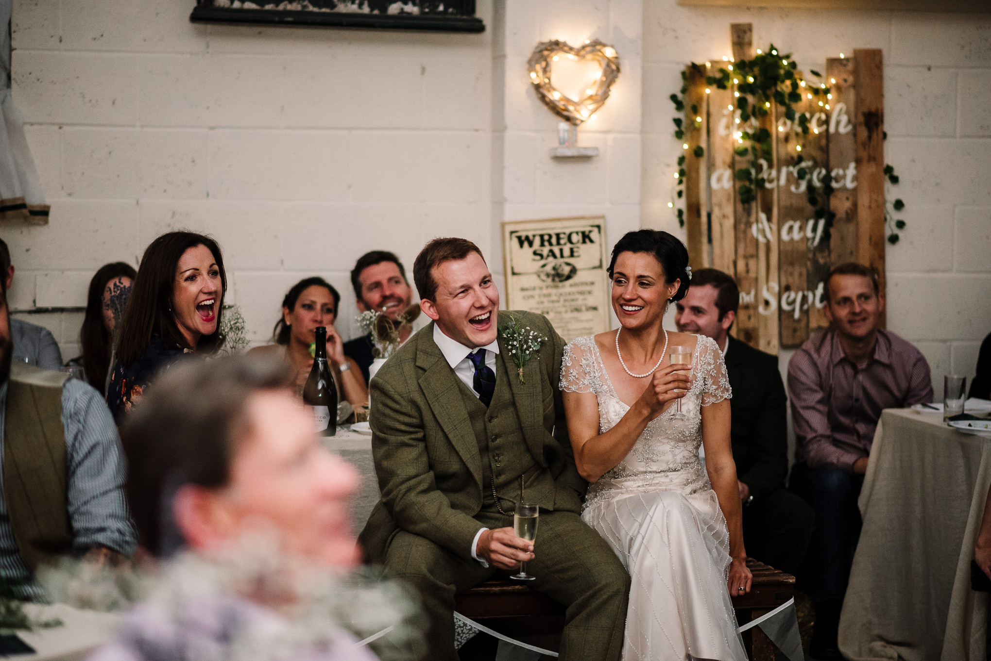 Relaxed photo of bride and groom durning speeches.