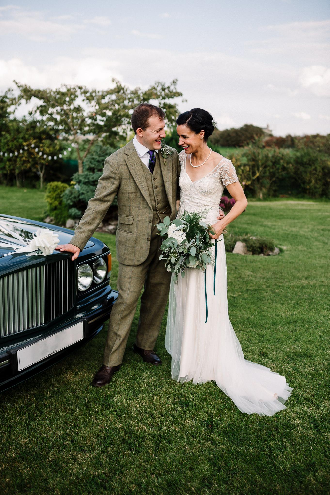 Bride and groom with wedding car. Farm wedding photography