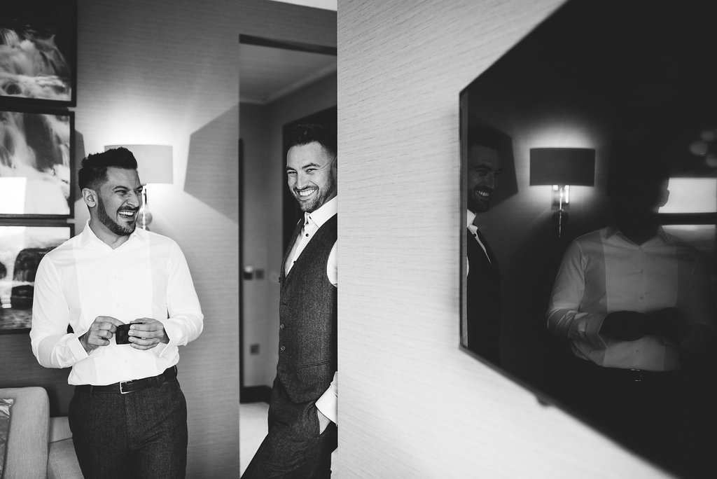 Natural black and White photo of groom and best man laughing. Lancashire wedding photography