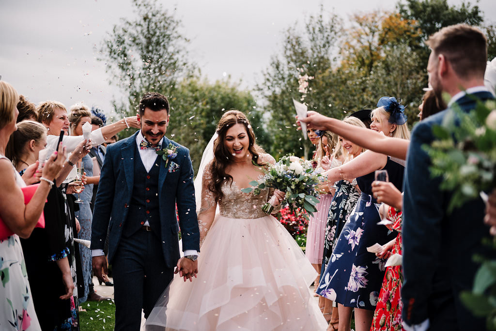 Bride and groom walking through a isle of confetti. Natural wedding photography
