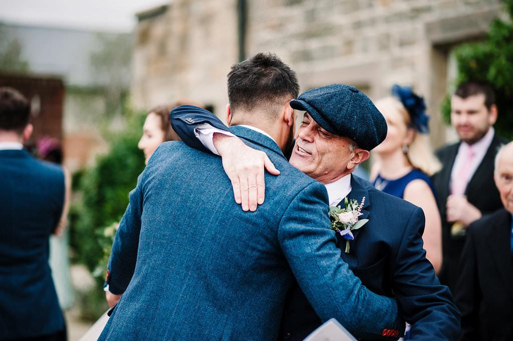 natural shot of groom his Dad hugging