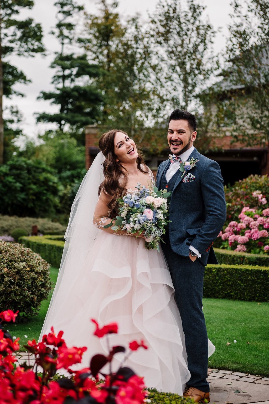 Colourful and relaxed portrait of bride and groom in the gardens at Stanley House Hotel.