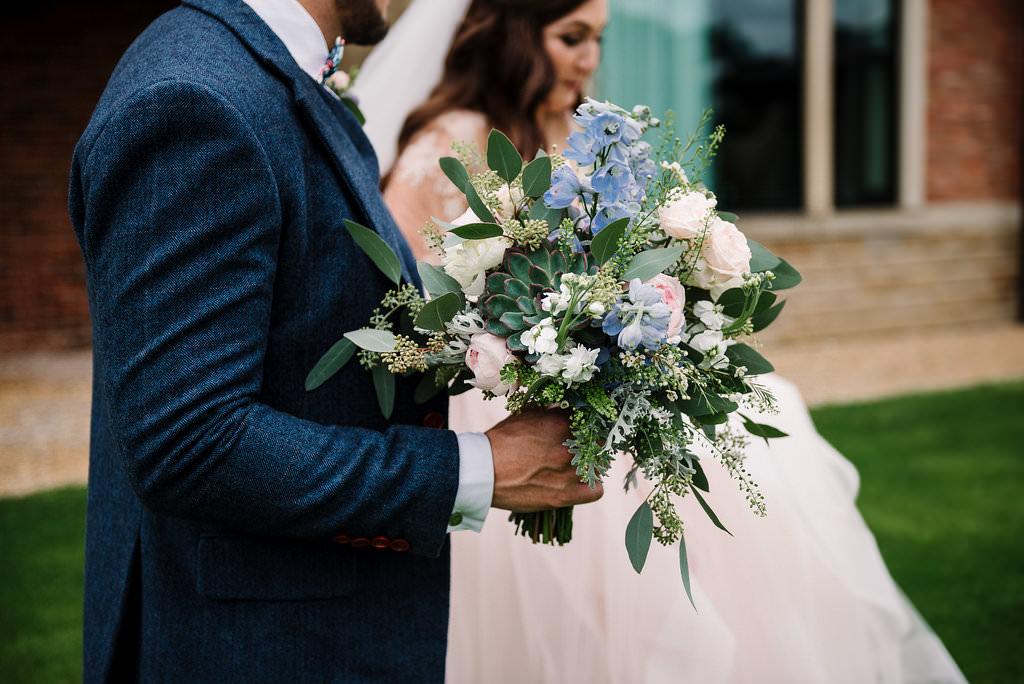 natural shot of bouquet as couple walk.