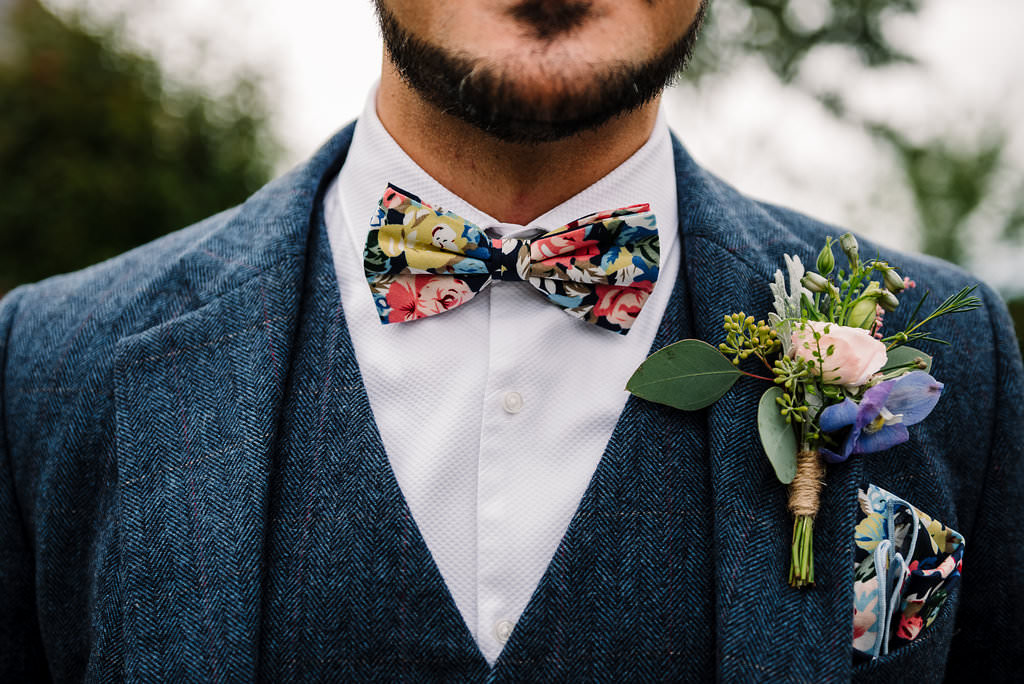 Detailed shot of floral bow tie and button hole on vintage style suit. Modern wedding photography