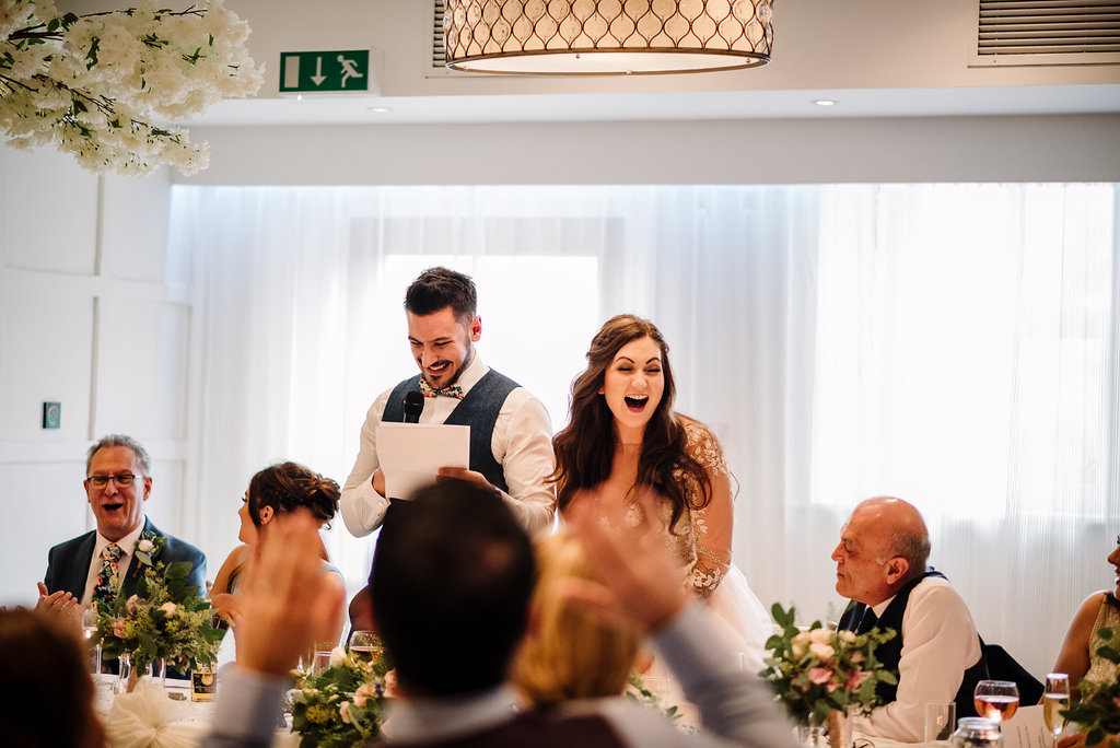 Natural photo of the bride and groom during speeches laughing.