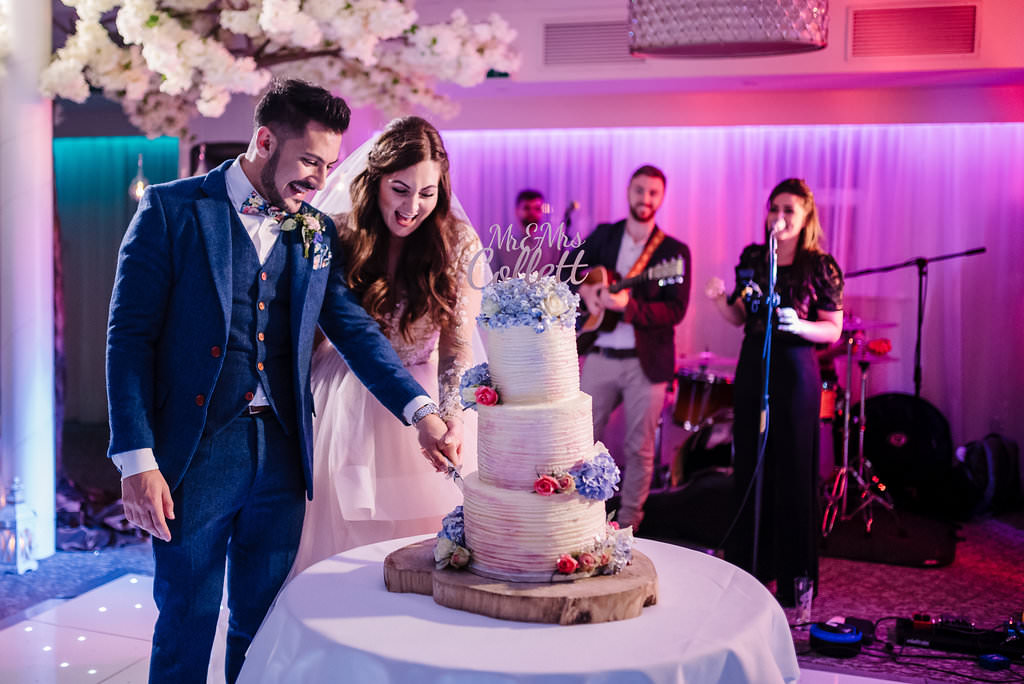 colourful portrait of the bride and groom cutting their wedding cake. Lancashire wedding photography