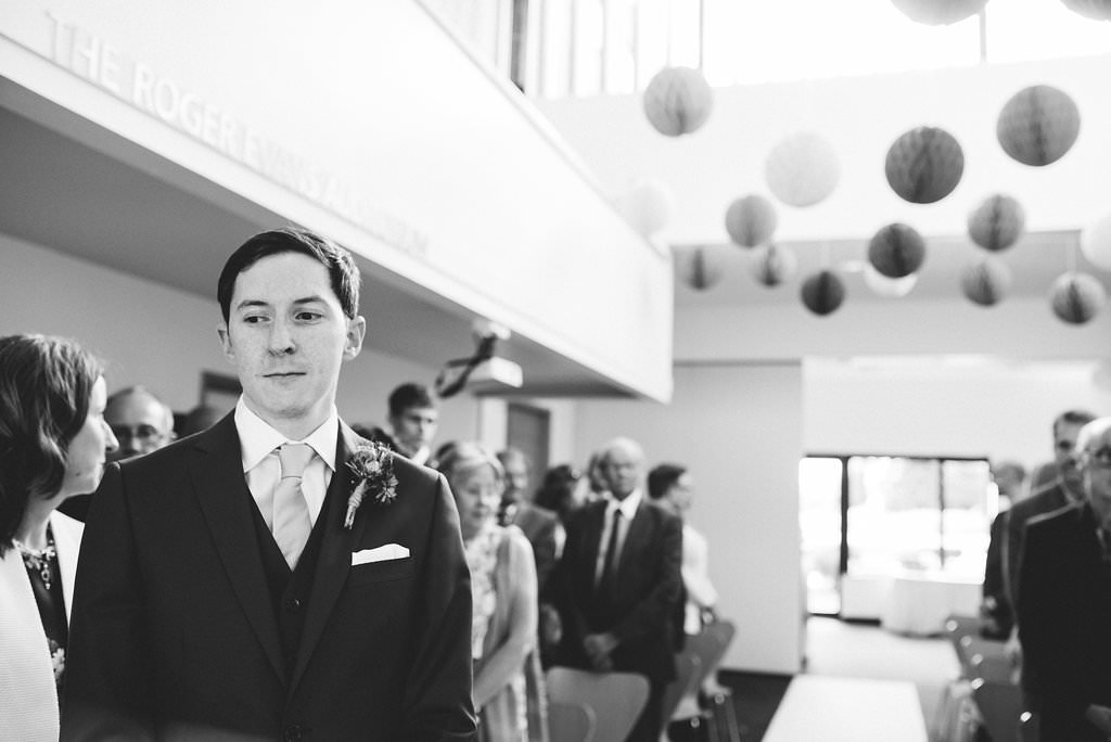 Black and white photo of groom waiting for his bride