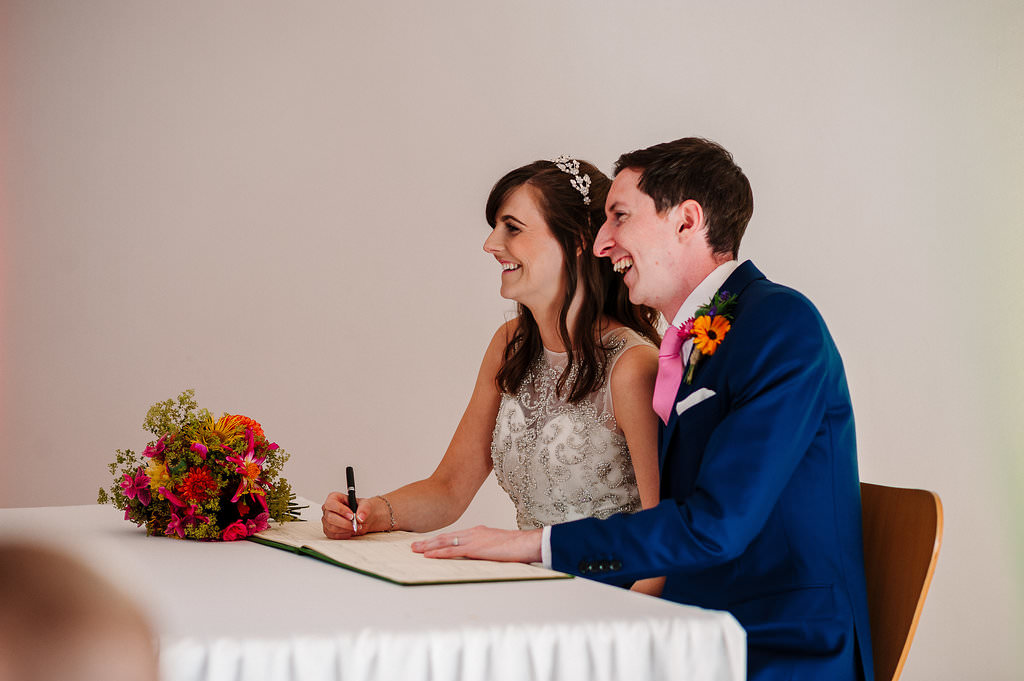 Natural photo of the Bride and Groom signing the register